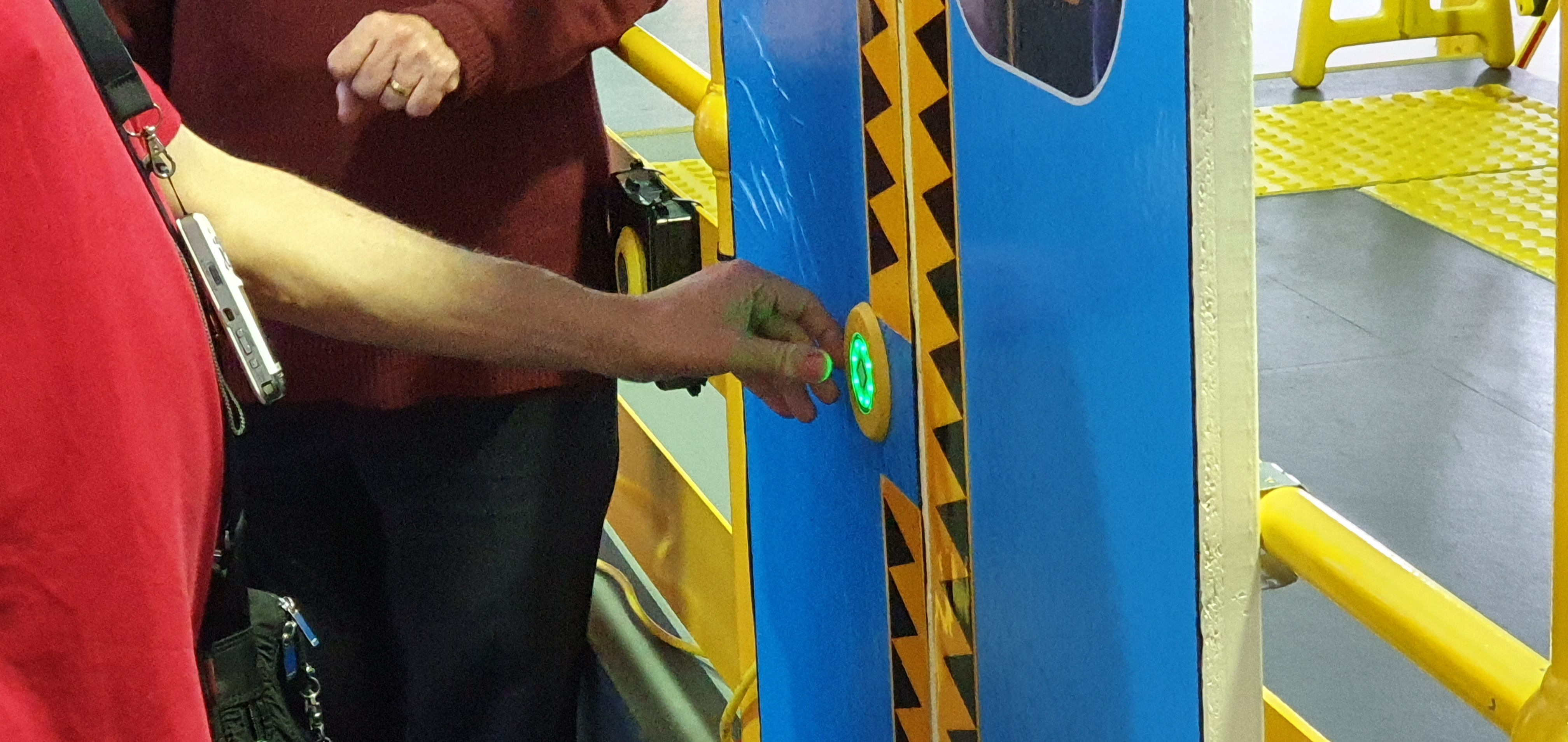 """A close-up of a hand pressing the open button on a train door."""